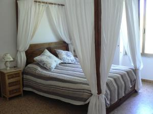 "Romantic ""colonial style"" with four poster bed."